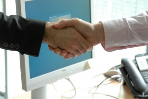 a handshake in front of a computer screen