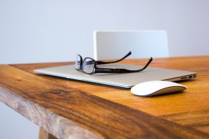 macbook, mouse, and glasses on a wood desk